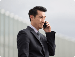 A man in a black suit talks on a smartphone outside. Traditional telecommunications infrastructure means the costs to maintain and support separate wireless and wireline phone systems. Rogers Unison saves money by consolidating desk phones, soft phones and smartphones into one system.