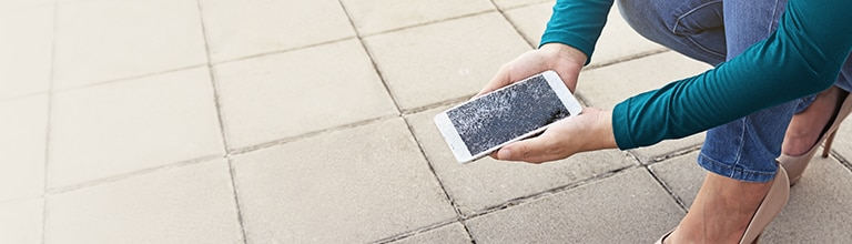 A person picking up their phone with a broken screen. Premium Device Protection plans can cover broken screen repairs and more.