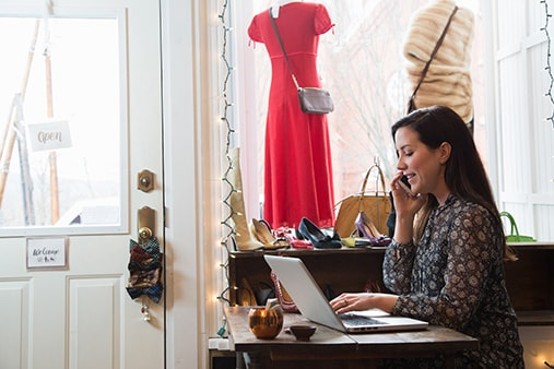 A small business owner uses business internet at her desk in her clothing store.