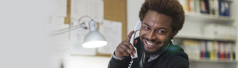 A man smiles while talking into his office phone that has one of our flexible phone plans.