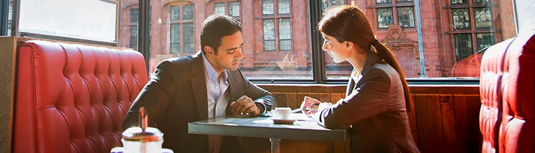 Two people in a café discussing business.