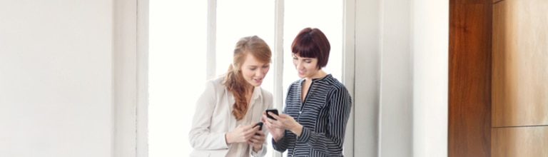 Two women looking at Rogers Small Business promotions on their mobile phones