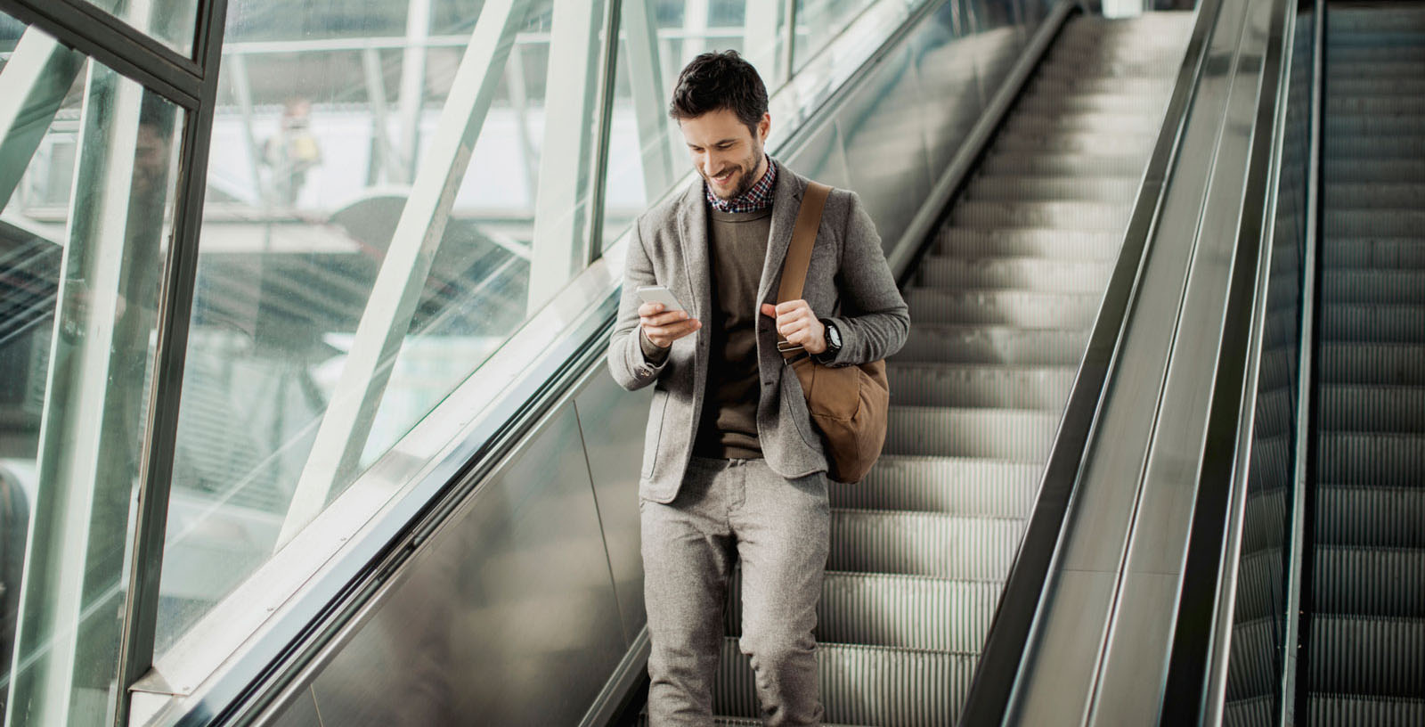 Businessman checking his phone while walking down an escalator