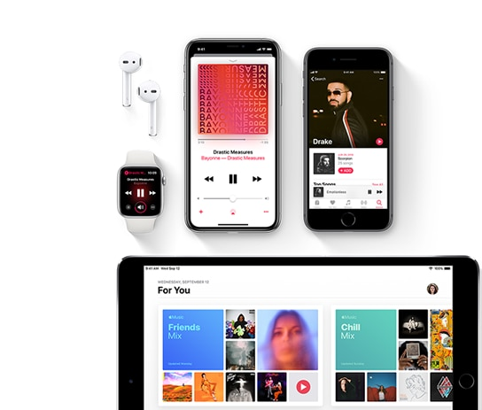 The Apple Music interface being displayed on the screens of multiple electronic devices.