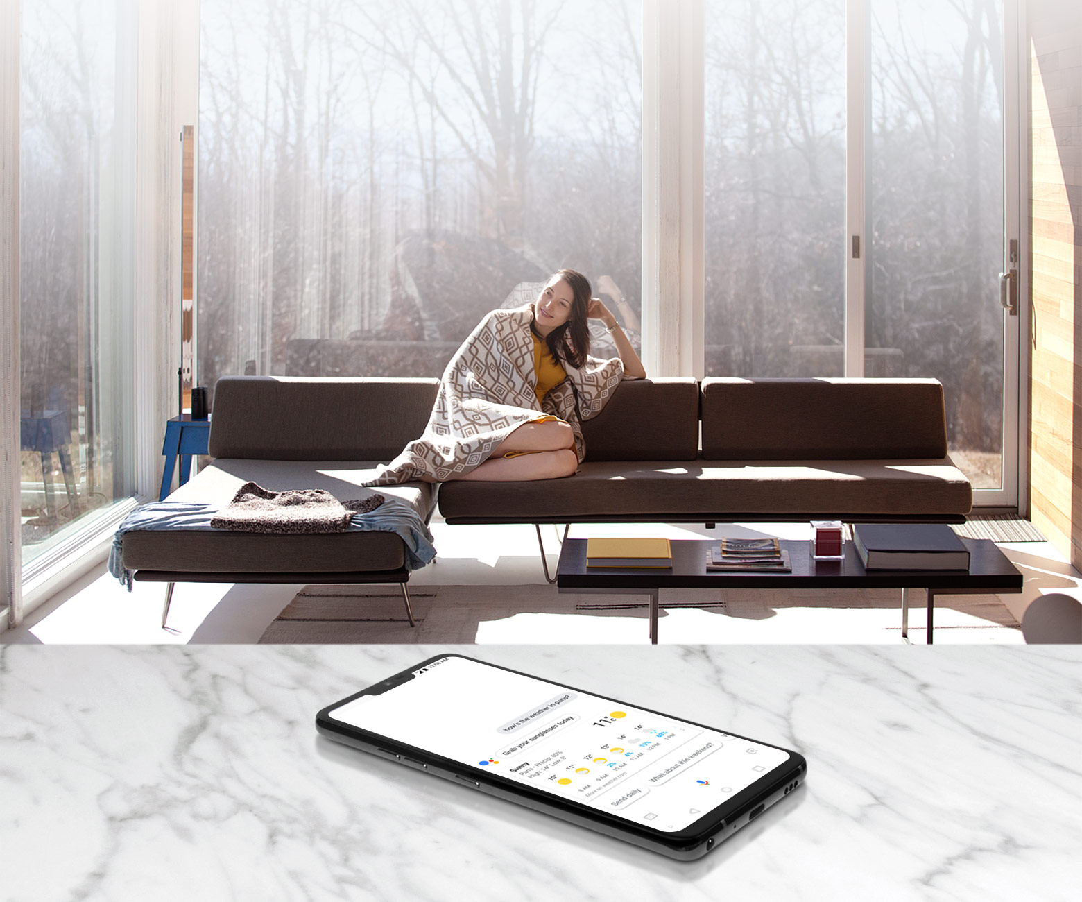 A woman sits on a couch and issues voice commands to a G7 ThinQ resting on a table several feet away.