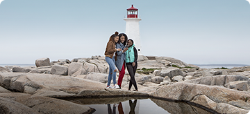 Three women posing in front of lighthouse at Peggy's Cove, NS.